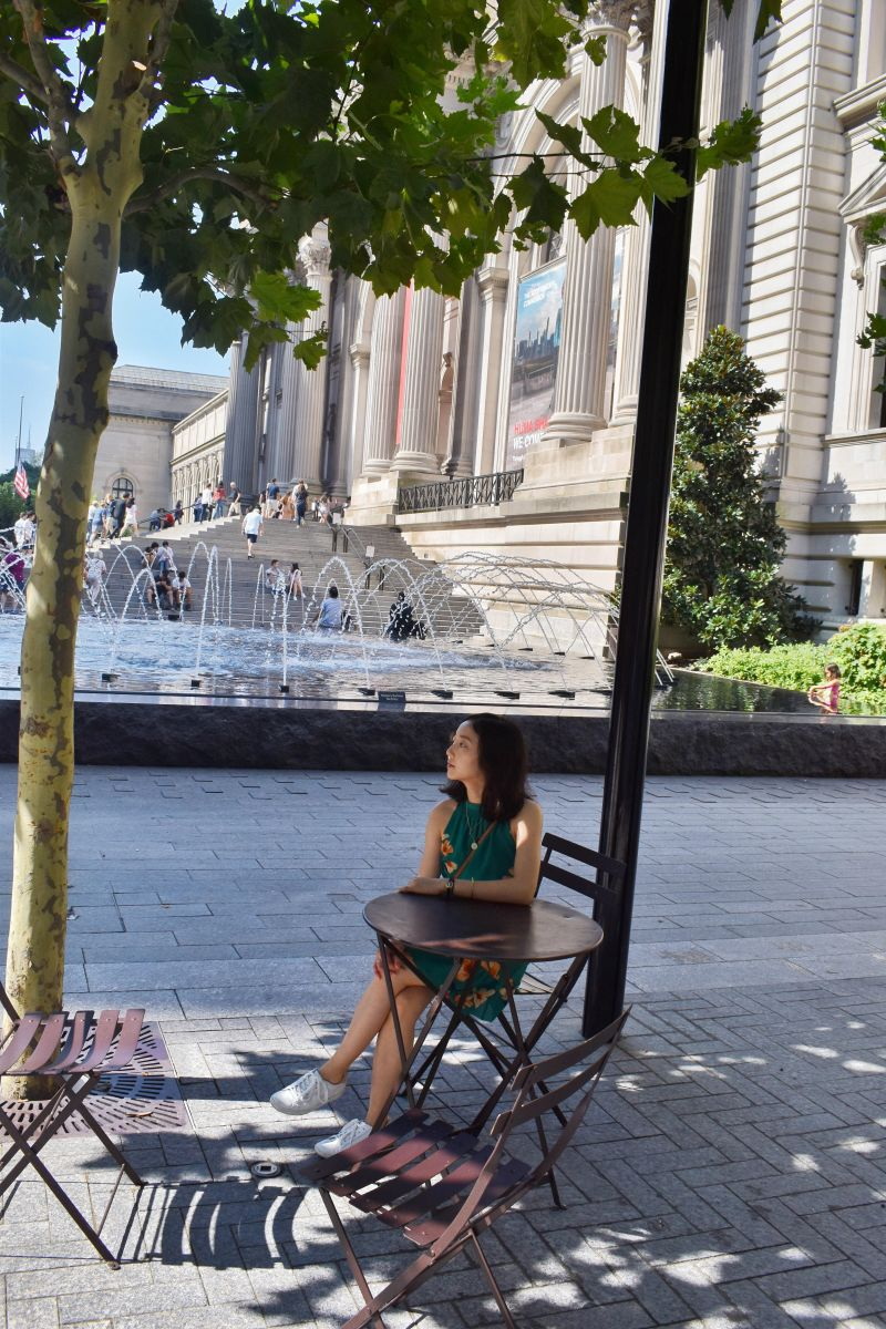 Looking off into the distance as I sit by the MET wearing an Aritzia floral dress and Keds women's ace sneakers in white