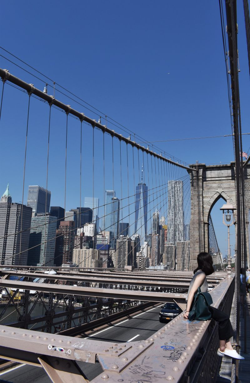 Photo of the skyscrapers in nyc on the Brooklyn Bridge. Ootd photo, Aritzia murphy blouse, Aritzia high waisted pants, Keds white sneakers and Matt and Nat backpack.
