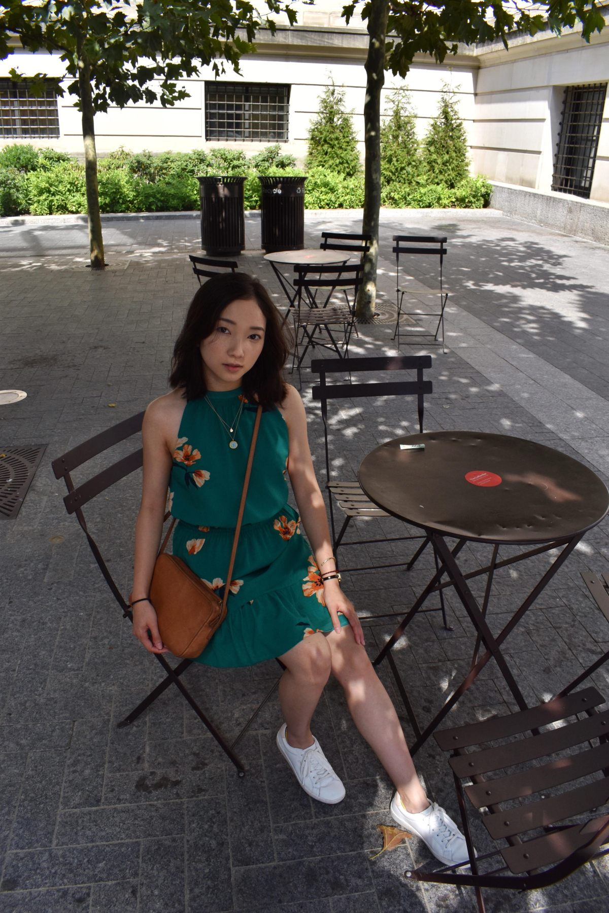 Outfit shot by the met featuring green floral Effet dress by Aritzia, brown leather crossbody by Aritzia and white women's ace sneakers by Keds